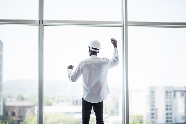 Jovem em hemlet protetora em frente a janelas panorâmicas com mãos reaised de vitória e sucesso