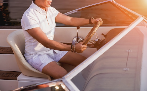Jovem em iate à vela. as mãos seguram o volante