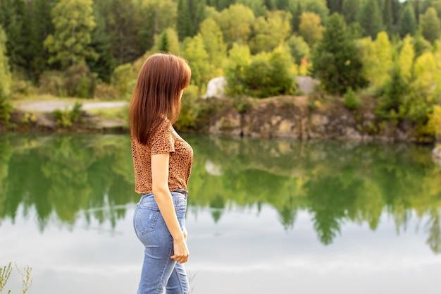 Jovem em jeans caminha perto de um belo lago em tempo nublado.