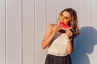 Jovem em óculos de sol, comendo uma melancia, aproveitando os dias ensolarados