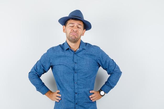 Jovem em pé com as mãos na cintura em uma camisa azul, chapéu e parecendo triste. vista frontal.