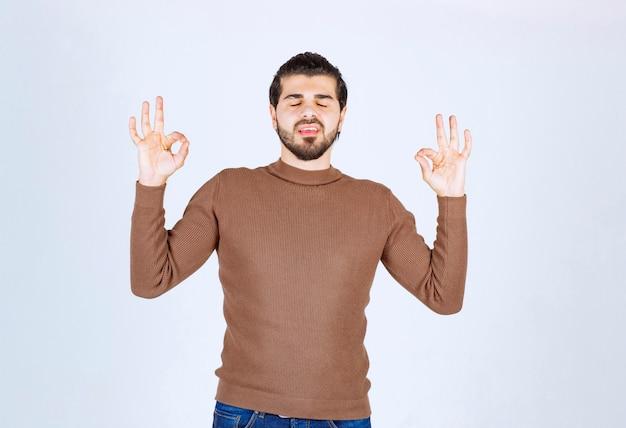 Jovem em pé com os olhos fechados e mostrando um gesto ok.