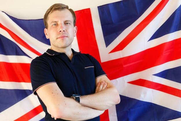 Jovem em pé contra a bandeira do reino unido