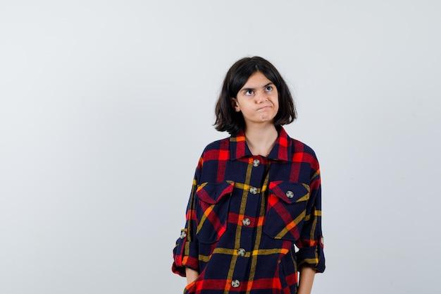Jovem em pé em linha reta e posando com uma camisa xadrez e parecendo uma fofa. vista frontal.