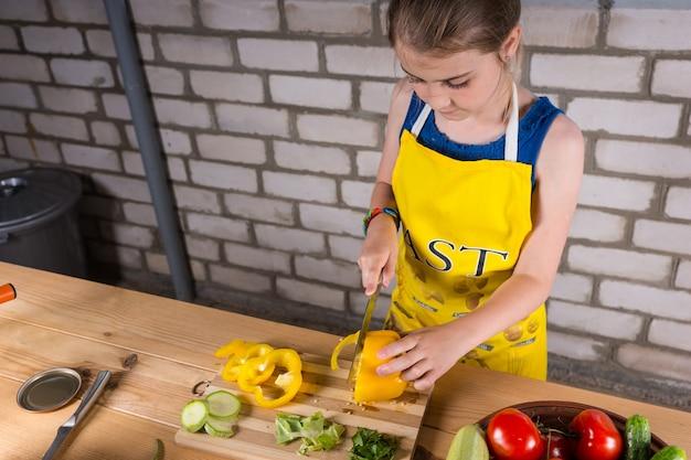 Jovem em pé em uma mesa ao ar livre, fatiando legumes frescos e cortando um pimentão doce
