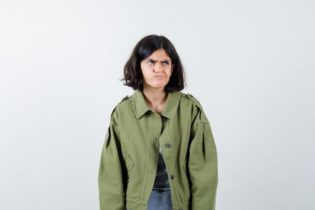 Jovem em pé, olhando para o lado e posando de suéter cinza, jaqueta cáqui, calça jeans e parecendo irritada, vista frontal.