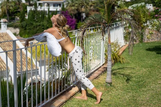 Jovem em pijama com um travesseiro relaxa no jardim