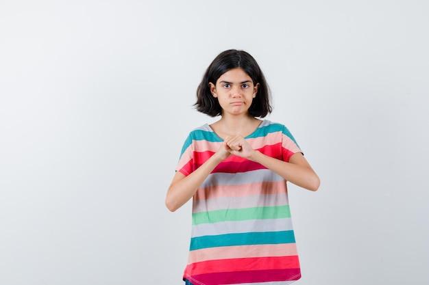 Jovem em pose de boxeador em t-shirt listrada colorida e olhando sério. vista frontal.