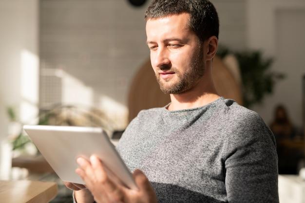 Jovem em roupa casual assistindo algo online enquanto passa um tempo em um café em um dia ensolarado