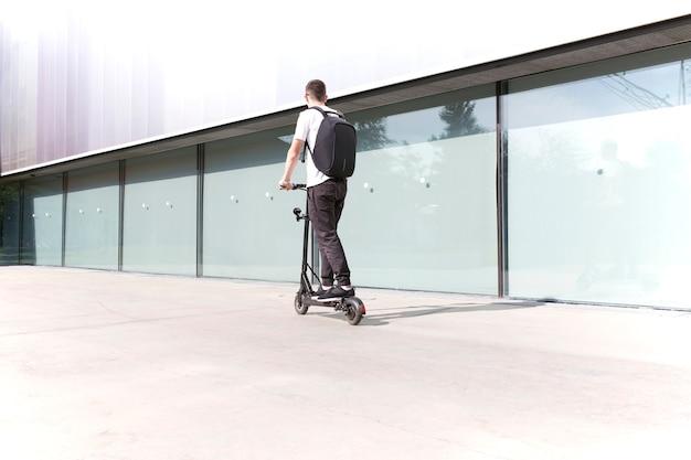 Jovem em roupa casual em uma scooter elétrica na rua da cidade