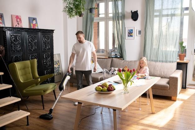 Jovem em roupa casual usando aspirador de pó enquanto faz tarefas domésticas e sua filha desenhando com lápis de cor por perto