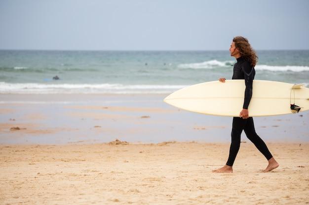 Jovem em roupa de neoprene preto andando na praia com prancha de surf durante o dia