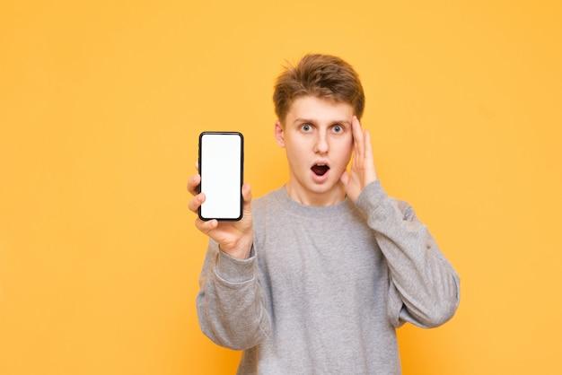 Jovem em roupas casuais tem na mão um smartphone moderno com uma tela branca e parece chocado com a câmera