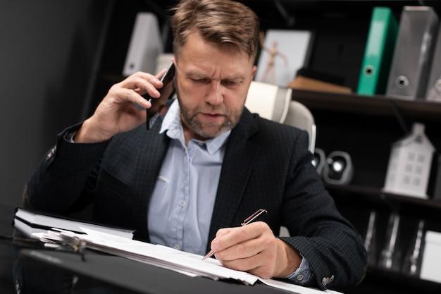 Jovem em roupas de negócios, trabalhando no computador mesa com telefone e documentos
