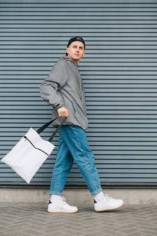 Jovem em roupas de rua elegantes e boné andando com eco bag na mão na parede cinza