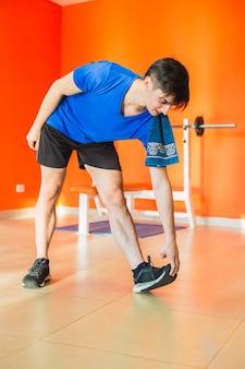 Jovem em roupas esportivas, alongamento antes de treinar na academia - retrato de um centro de fitness, fazendo exercícios de alongamento no ginásio.