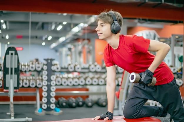 Jovem em roupas esportivas e fones de ouvido está envolvido com halteres no ginásio
