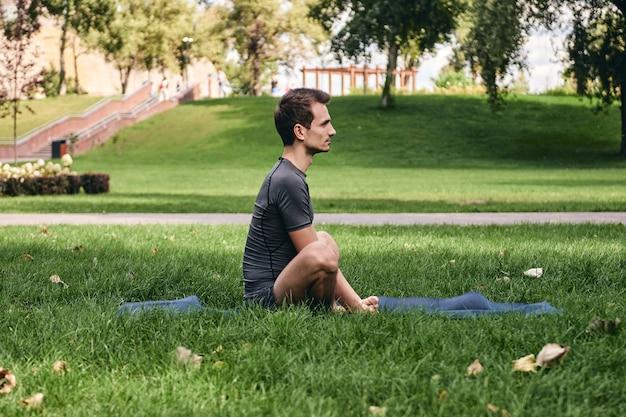 Jovem em roupas esportivas fazendo ioga no parque