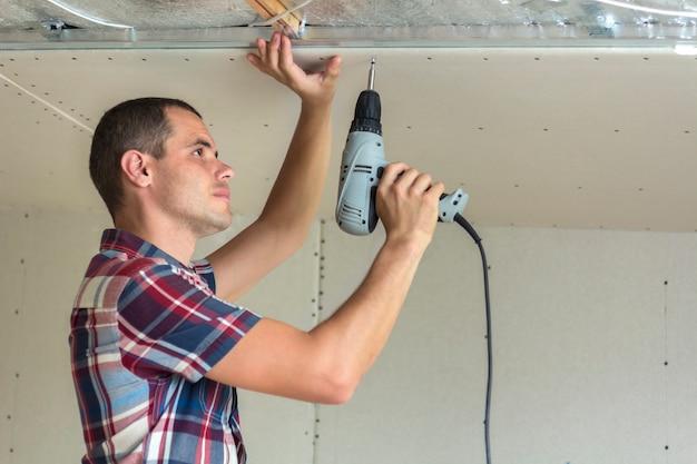 Jovem em roupas habituais e luvas de trabalho, fixação de drywall suspendido teto para armação de metal usando a chave de fenda elétrica no teto isolado com folha de alumínio brilhante. diy, faça você mesmo conceito.