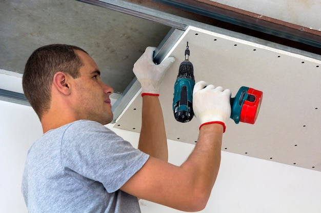 Jovem em roupas habituais e luvas de trabalho para fixação de teto suspenso em drywall para armação de metal usando a chave de fenda elétrica no teto isolado com folha de alumínio brilhante. diy, faça você mesmo conceito.