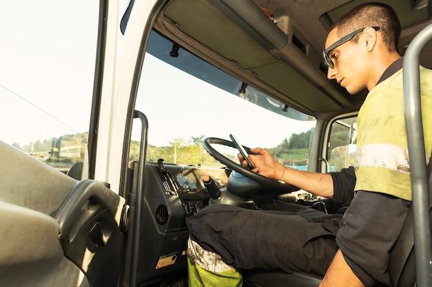 Jovem em seu caminhão dentro da cabine com as roupas de segurança usando o smartphone