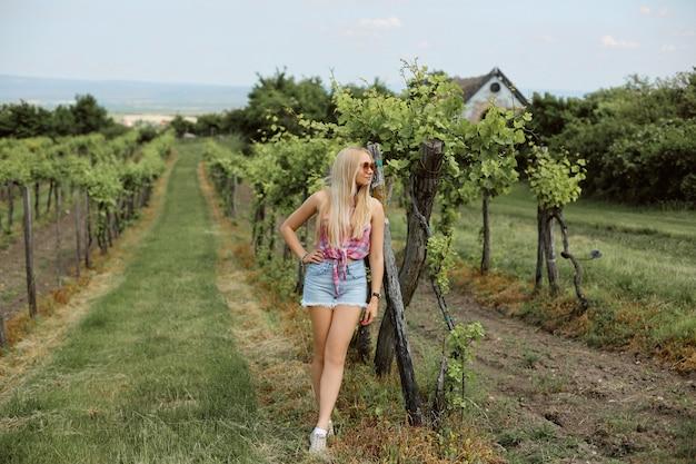 Jovem em shorts jeans e camisa sem mangas, posando na vinha em um dia de verão