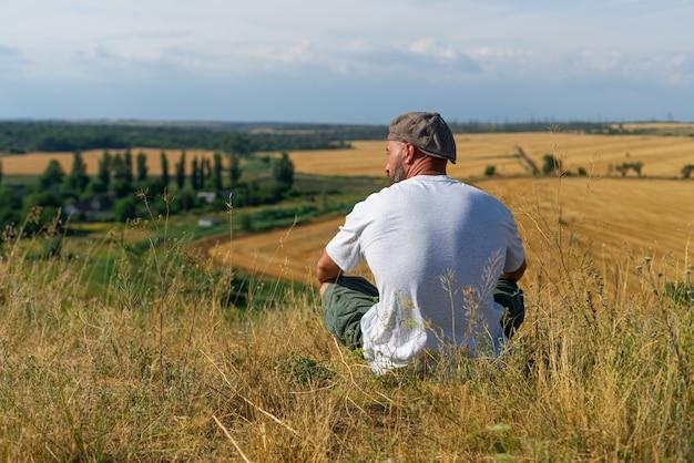 Jovem em sportswear preto está sentado na beira do penhasco e olhando para o vale enevoado abaixo