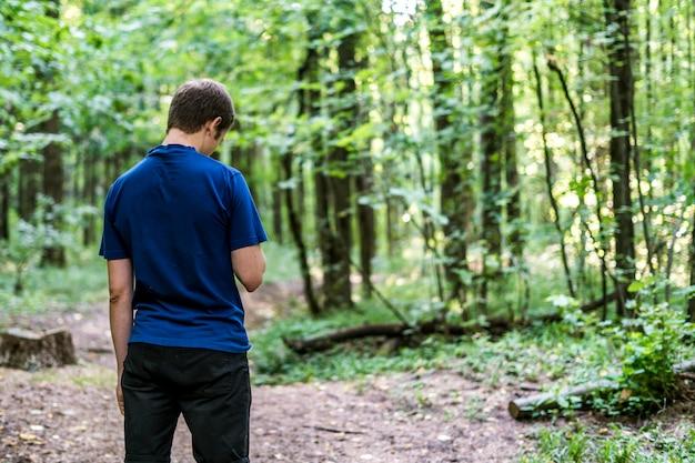 Jovem em t-shirt azul andar e olhar ao redor da floresta de outono