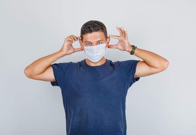 Jovem em t-shirt azul escuro, usando máscara médica e olhando cuidadoso, vista frontal.