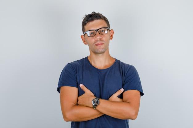 Jovem em t-shirt azul, óculos, cruzando as mãos no peito e olhando sério, vista frontal.