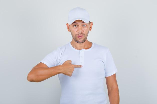 Jovem em t-shirt branca, boné mostrando o dedo como me perguntando e parecendo surpreso, vista frontal.