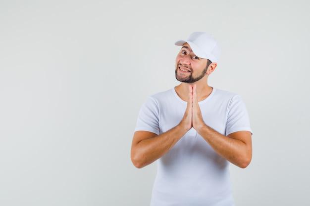 Jovem em t-shirt branca, boné mostrando o gesto namastê e parecendo feliz, vista frontal. espaço para texto