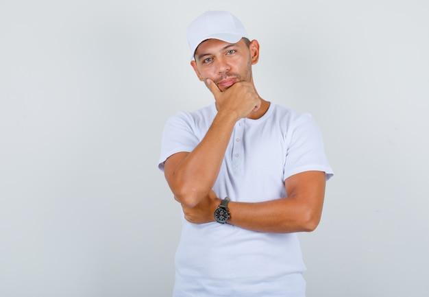 Jovem em t-shirt branca, boné, segurando a mão no queixo e parecendo confiante, vista frontal.