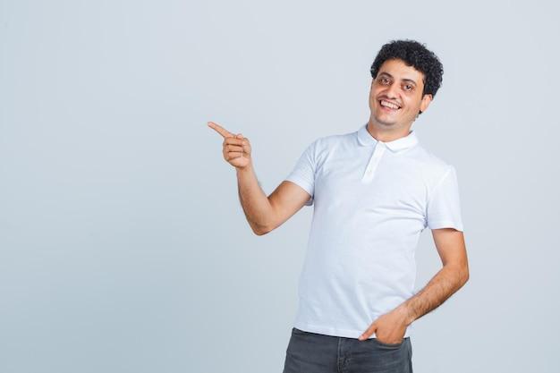 Jovem em t-shirt branca, calças apontando para o lado e parecendo feliz, vista frontal.