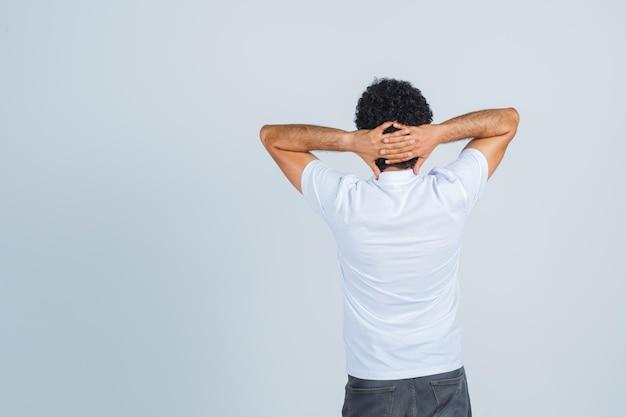 Jovem em t-shirt branca, calças, mantendo as mãos atrás da cabeça e parecendo confiante, vista traseira.