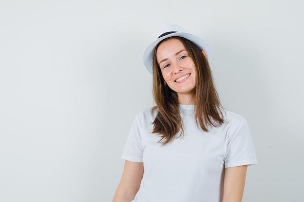 Jovem em t-shirt branca, chapéu e olhando alegre, vista frontal.