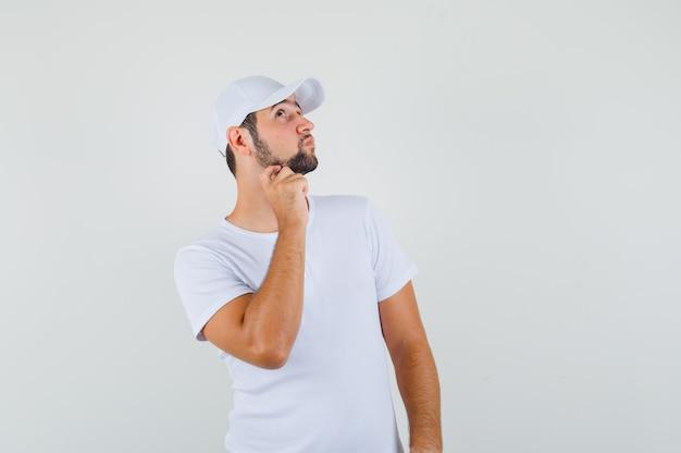 Jovem em t-shirt branca coçando o queixo e olhando pensativo, vista frontal.