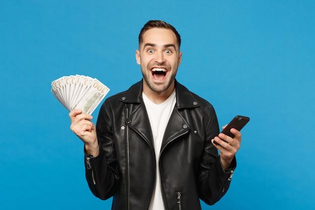 Jovem em t-shirt branca de jaqueta de couro preta segurando leque de dinheiro em notas de dólar, celular isolado no retrato de estúdio de fundo de parede azul. conceito de estilo de vida de pessoas. simule o espaço da cópia.