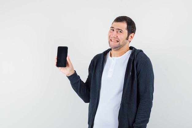 Jovem em t-shirt branca e capuz preto com zíper na frente segurando o smartphone, sorrindo e parecendo feliz, vista frontal.