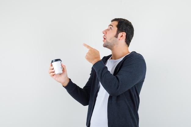 Jovem em t-shirt branca e capuz preto com zíper segurando a xícara de café para viagem e apontando para a direita com o dedo indicador e olhando surpreso, vista frontal.