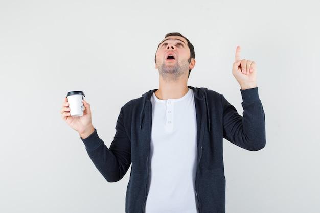 Jovem em t-shirt branca e capuz preto com zíper segurando a xícara de café para viagem e apontando para cima com o dedo indicador e olhando surpreso, vista frontal.