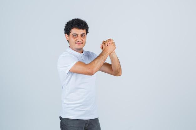 Jovem em t-shirt branca e jeans, apertando as mãos e parecendo feliz, vista frontal.