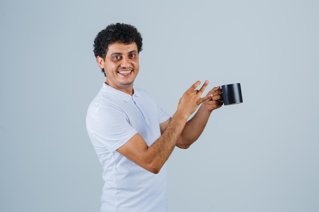 Jovem em t-shirt branca e jeans segurando uma xícara de chá enquanto aponta para ele e parece feliz, vista frontal.