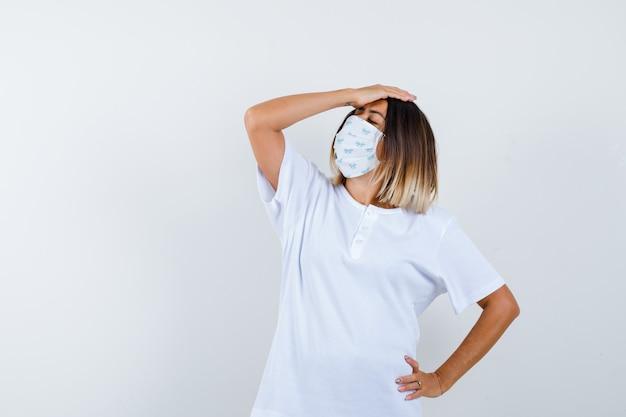Jovem em t-shirt branca e máscara, colocando uma mão na cabeça, a outra mão na cintura e olhando preocupada, vista frontal.