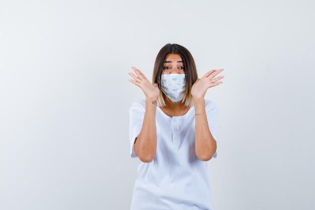 Jovem em t-shirt branca e máscara de mãos dadas perto da cabeça e olhando feliz, vista frontal.