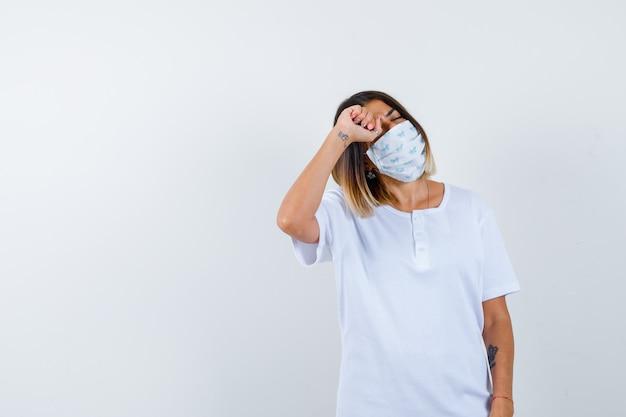 Jovem em t-shirt branca e máscara esfregando os olhos com o punho e parecendo cansada, vista frontal.
