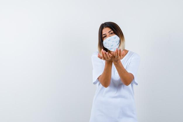 Jovem em t-shirt branca e máscara, esticando as mãos em concha e olhando alegre, vista frontal.