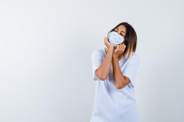 Jovem em t-shirt branca e máscara repousando o rosto nas mãos e olhando com sono, vista frontal.