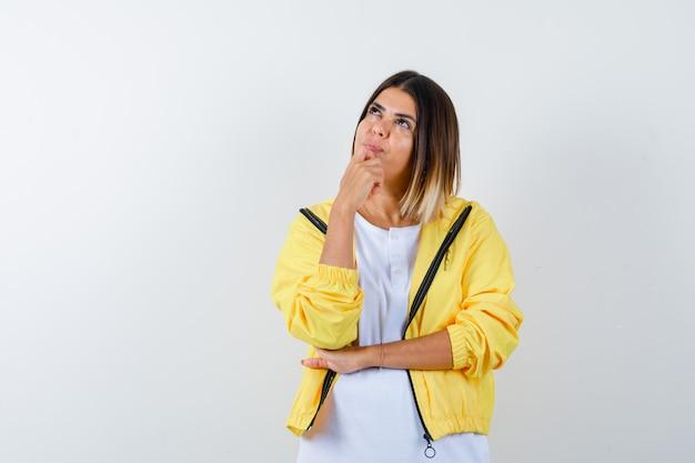 Jovem em t-shirt branca, jaqueta amarela em pé em pose de pensamento, apoiando o queixo na mão e olhando pensativa, vista frontal.
