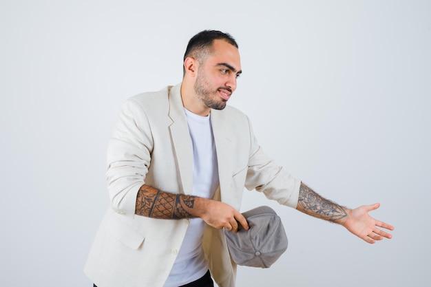 Jovem em t-shirt branca, jaqueta e boné cinza, segurando o boné na mão e esticando a mão para convidar alguém e parecendo feliz, vista frontal.